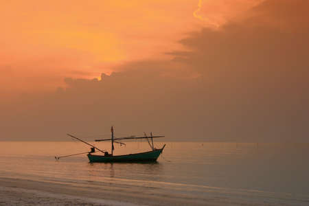 Fishing boat and sunset at the beach. photo