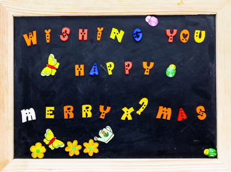 Color merry christmas words on black board. photo
