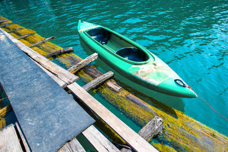 2 persons: Green canoe for 2 persons on lake at port. Stock Photo