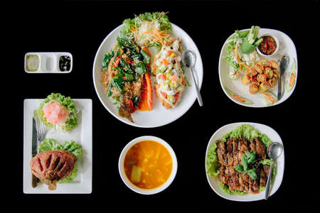 Many thai food from top view with black background.