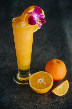 Glasses of fresh orange juice on dark background.