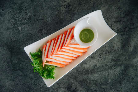 Crab stick with wasabi on dark table.