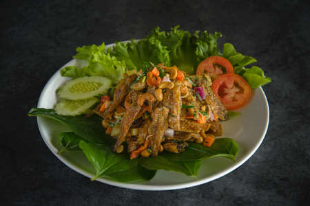 fried fish spicy salad with herb.