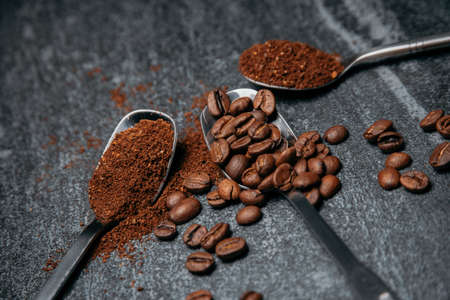 Teaspoons with coffee beans, spoons with ground coffee, morning coffee drink ingredients for espresso 免版税图像