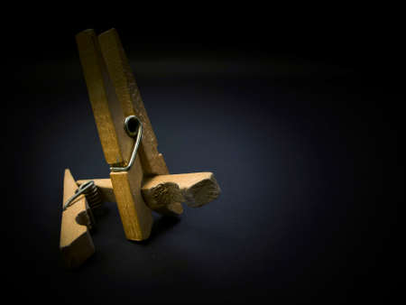 provoking: Fighting of wooden clothespins on dark background. Illustration aggression issues. Part of photoset.