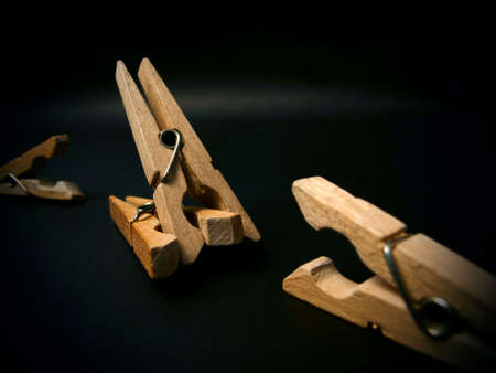 onslaught: Fighting of wooden clothespins on dark background. Illustration aggression issues. Part of photoset.