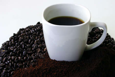 jolt: Mug of Coffee Surrounded by Coffee Beans Stock Photo