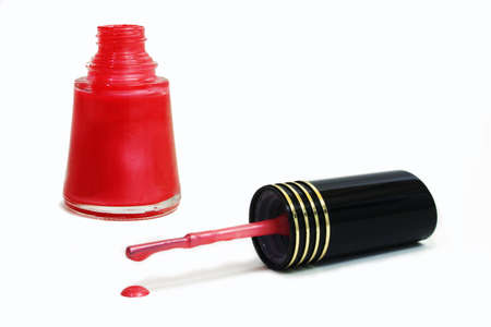 A bottle of nail polish with its dripping brush laying on the table.