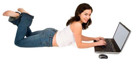 ラップトップを使用して床に笑みを浮かべて女性