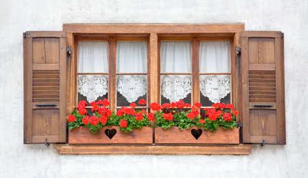 Oude Europese houten ramen met luiken en bloemen. Stockfoto
