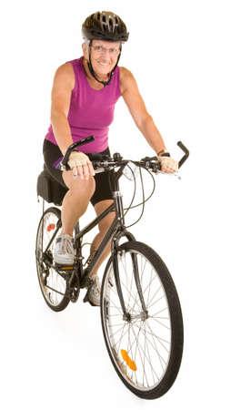 自転車に乗ってフィットの年配の女性の笑みを浮かべてください。 写真素材