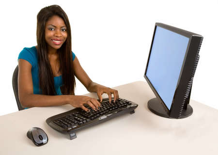 A smiling African American businesswoman is working at her computer.