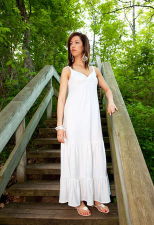 Beautiful Woman in a White Dress Standing on Wooden Steps in the Forest