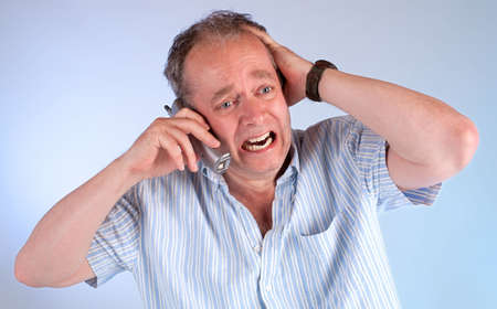 upset man: Receiving Bad News over the Telephone Stock Photo