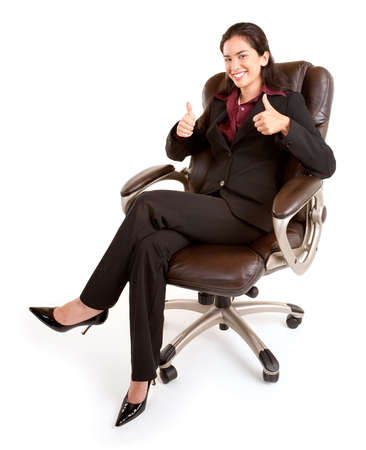 sit: Businesswoman Sitting on a Leather Chair with Thumbs Up Stock Photo