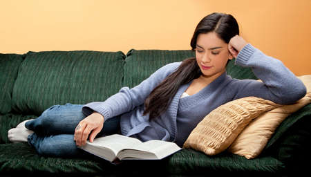 Young Woman Lying Down on Sofa and Reading Book