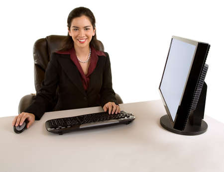 Businesswoman Sitting at her Desk and Smiling at the Camera photo