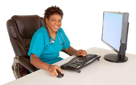 笑みを浮かべてアフリカ系アメリカ人の看護師を見てカメラ間彼女の机に座って