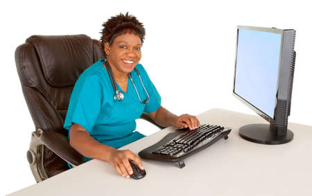 general practitioner: Smiling African American Nurse Looking at Camera While Sitting at her Desk Stock Photo
