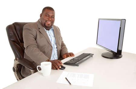 彼の机に座っている笑顔のアフリカ系アメリカ人の実業家 写真素材