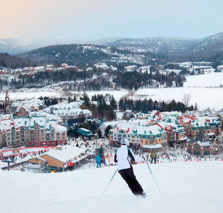 Mont-Tremblant, Canada - February 9, 2014  Skiers and snowboarders are sliding down the main slope at Mont-Tremblant Ski Resort  It is acknowledged by most industry experts as being the best ski resort in Eastern North America