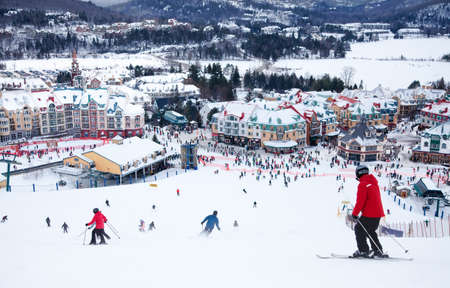 Mont-Tremblant, Canada - February 9, 2014  Skiers and snowboarders are sliding down the main slope at Mont-Tremblant  Mont-Tremblant Ski Resort is acknowledged by most industry experts as being the best ski resort in Eastern North America