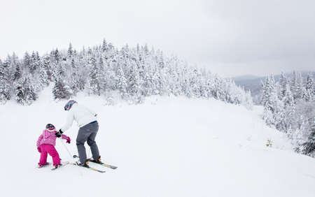 Mont-Tremblant, Canada - February 9, 2014  A mother is teaching her young daughter to ski down an easy slope at Mont-Tremblant Ski Resort  It is acknowledged, by most industry experts, as being the best ski resort in Eastern North America