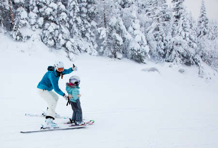 Mont-Tremblant, Canada - February 9, 2014  A mother is teaching her child to ski down an easy slope at Mont-Tremblant Ski Resort  It is acknowledged, by most industry experts, as being the best ski resort in Eastern North America