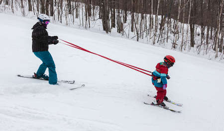 Mont Tremblant, Quebec, Canada - February 9, 2014: A mother is teaching her young daughter to ski down an easy slope at Mont-Tremblant Ski Resort. Mont-Tremblant Ski Resort is acknowledged, by most industry experts, as being the best ski resort in Eastern