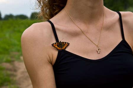 Farfalla sul petto di donna Archivio Fotografico