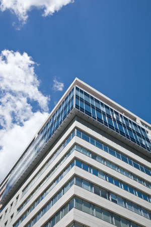Corner of office tower with blue sky and clouds Stock Photo