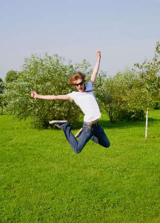 giovani adulti ragazzo saltando sul prato soleggiato. Motion Blur.
