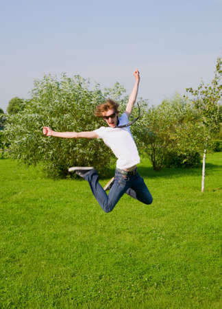 young adult boy jumping on sunny meadow. Motion blur.