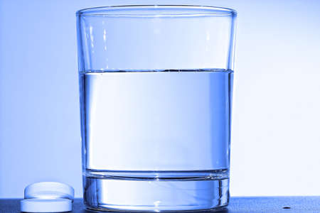Two effervescent tablets and glass with water. Blue tonned