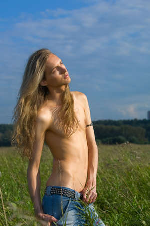Young adult boy stand in green field Stock Photo