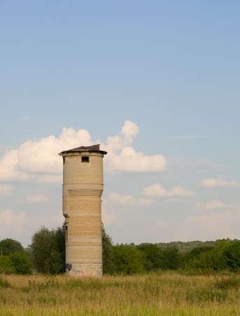 Rovinato acqua mattone-pompa torre nel prato verde