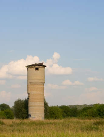 Ruined brick water-pump tower in the green meadow