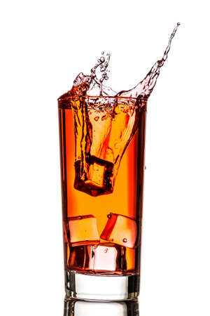 Ice splashing in cup of tea over white background
