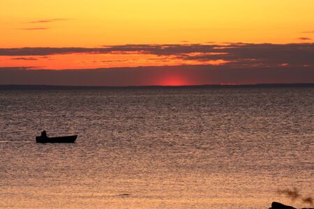 Small fishing boat at sunrise Stock Photo