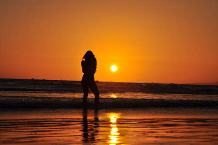 mrs santa: Woman at the beach during sunset Stock Photo