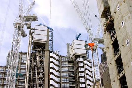 High-rise office buildings under construction, using large industrial cranes