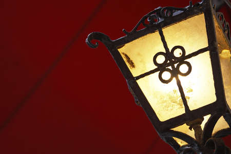 A traditional cast iron style light against a deep red background.