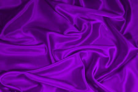 Luxurious deep purple satinsilk folded fabric, useful for backgrounds