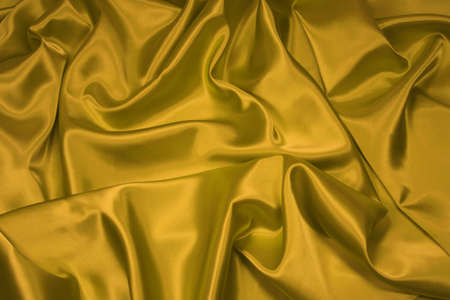 Luxurious golden satinsilk folded fabric, useful for backgrounds