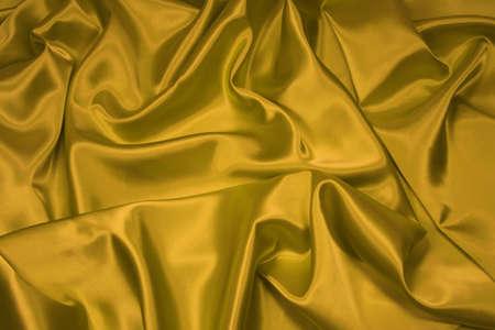 Luxurious golden satinsilk folded fabric, useful for backgrounds