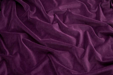 Luxurious rich purple velvet folded fabric, useful for backgrounds