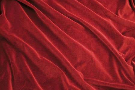 Luxurious rich red velvet folded fabric, useful for backgrounds Stock Photo