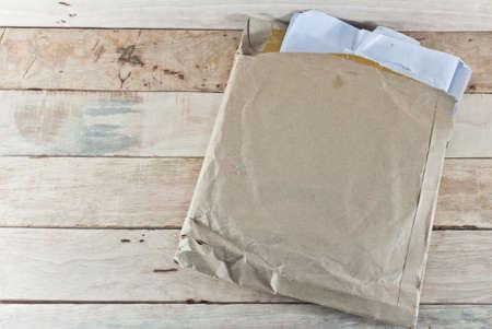 old envelope: Document in old envelope on wooden desk background.Selective focus.