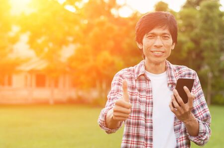 Happy asian man with news or message from smart phone in garden,soft focus,success concept.