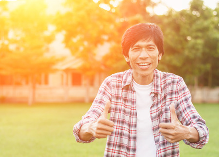gamers: Happy asian man in garden,soft focus,success concept.